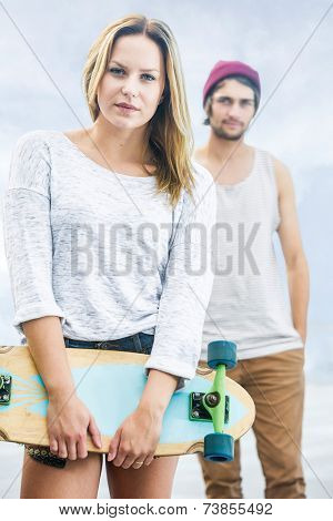lifestyle portrait of a girl with a skateboard in front of a guy