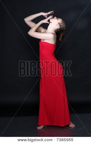 Young Beautiful Woman In Red Dress Dancing Over Black Background