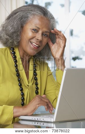 African woman using laptop at home