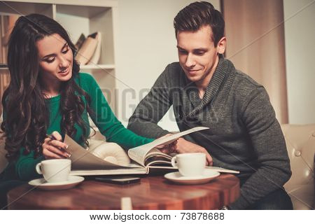 Young man and woman with book and coffee behind table