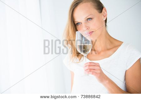 Gorgeous young woman with a glass of wine, smelling the lovely drink, savouring every sip (shallow DOF; color toned image)