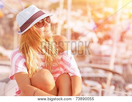 Portrait of attractive woman relaxing on luxury sailboat, enjoying mild sunset light, summer fashion and style concept