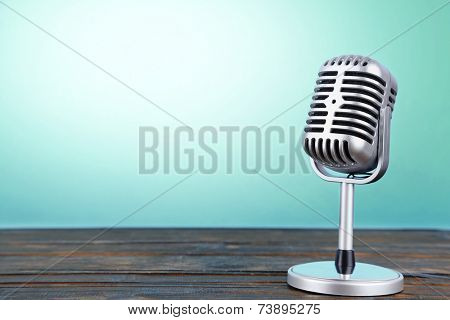 Old metal microphone on wooden table on light blue background