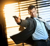 Determined caucasian action hero wearing suit and tie holding gun in hand. Standing, moving, aiming with revolver, inspector, cop, police, policeman, indoor, thriller, crime. poster