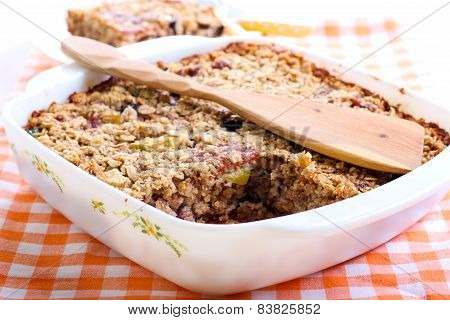 Fruity baked oatmeal in baking tin on table poster