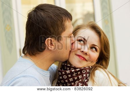 Photo of a chappy kissing young couple
