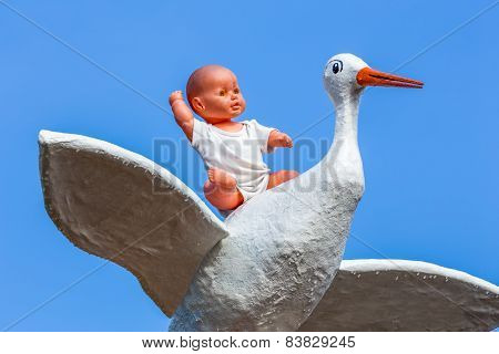 Baby doll sitting on back of stork with blue sky