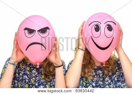 Two girls holding pink balloons with facial expression