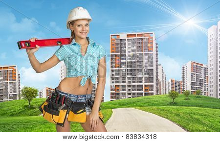 Woman in tool belt and helmet holding building level. Looking at camera, smiling. Buildings as backd