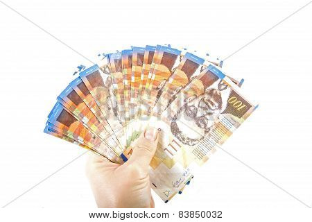 A female hand holding One hundred shekel bank notes against white background. Concept photo of money banking currency and foreign exchange rates. poster