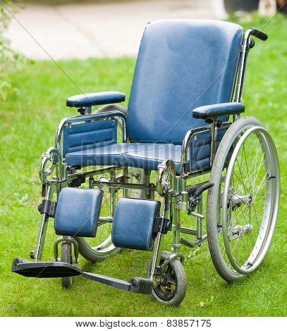 Photo of a wheelchair on green grass poster