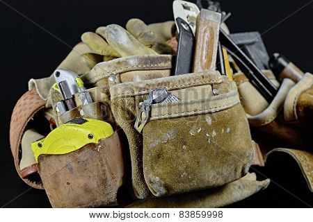 Rugged Leather Carpenters Work Bag With Worn Tools Isolated On Black Background