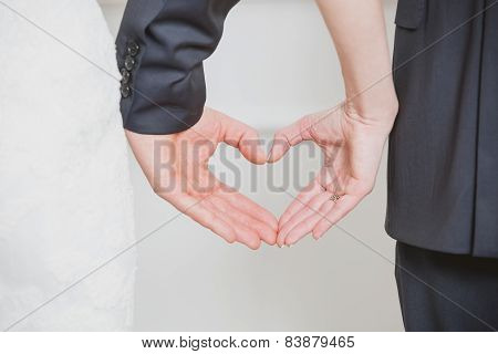 wedding couple showing shape of heart from their hands.