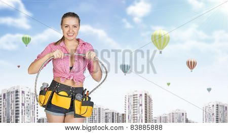 Woman in tool belt connects two flexible hoses. Buildings with air balloons as backdrop