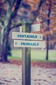 Signpost in a park or forested area with arrows pointing two opposite directions towards Certainly and Probably retro effect faded look. poster