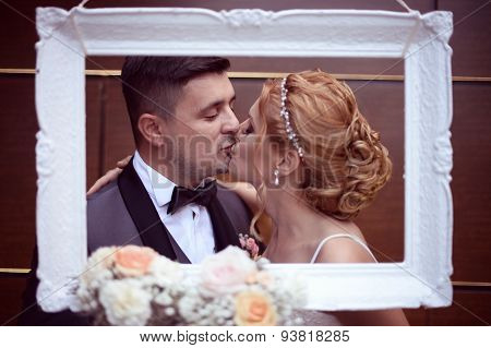 Bride And Groom Kissing Through The Frame