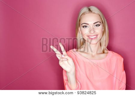 Smiling blond-haired woman pointing with fingers