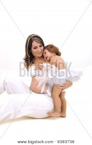 pregnant topless mother playing with her infant daughter
