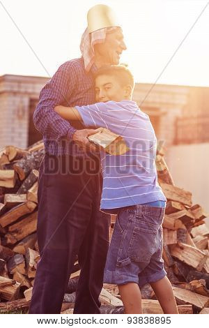 Nephew Huge Grandfather Outside In Front Of Stack Of Wood