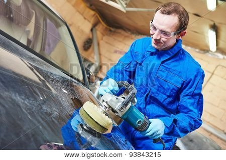auto mechanic worker polishing car body at automobile repair and renew service station shop by power buffer machine poster