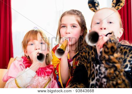 Kids with noisemakers making noise on party looking into the camera