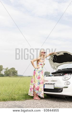 Full-length of tensed woman standing by broken down car on country road