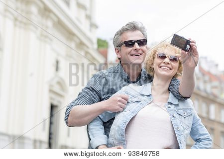 Happy middle-aged couple in sunglasses taking self portrait outdoors