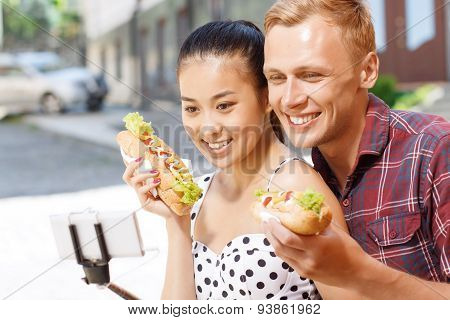 Man and woman with hotdogs doing selfie