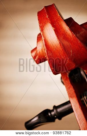 Extreme Close Up of Carved Wooden Scroll and Pegbox of Violin with Blurred Sheet Music in Background with Copy Space poster