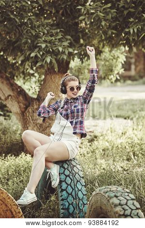 Hipster Girl Listening To Music With Headphones In A Summer Park.