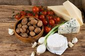 Horizontal photo with three kinds of cheese - camembert danish blue niva and eidam. Walnuts garlic spring onion and tomatoes are there too. All is on wooden board with jute around. poster