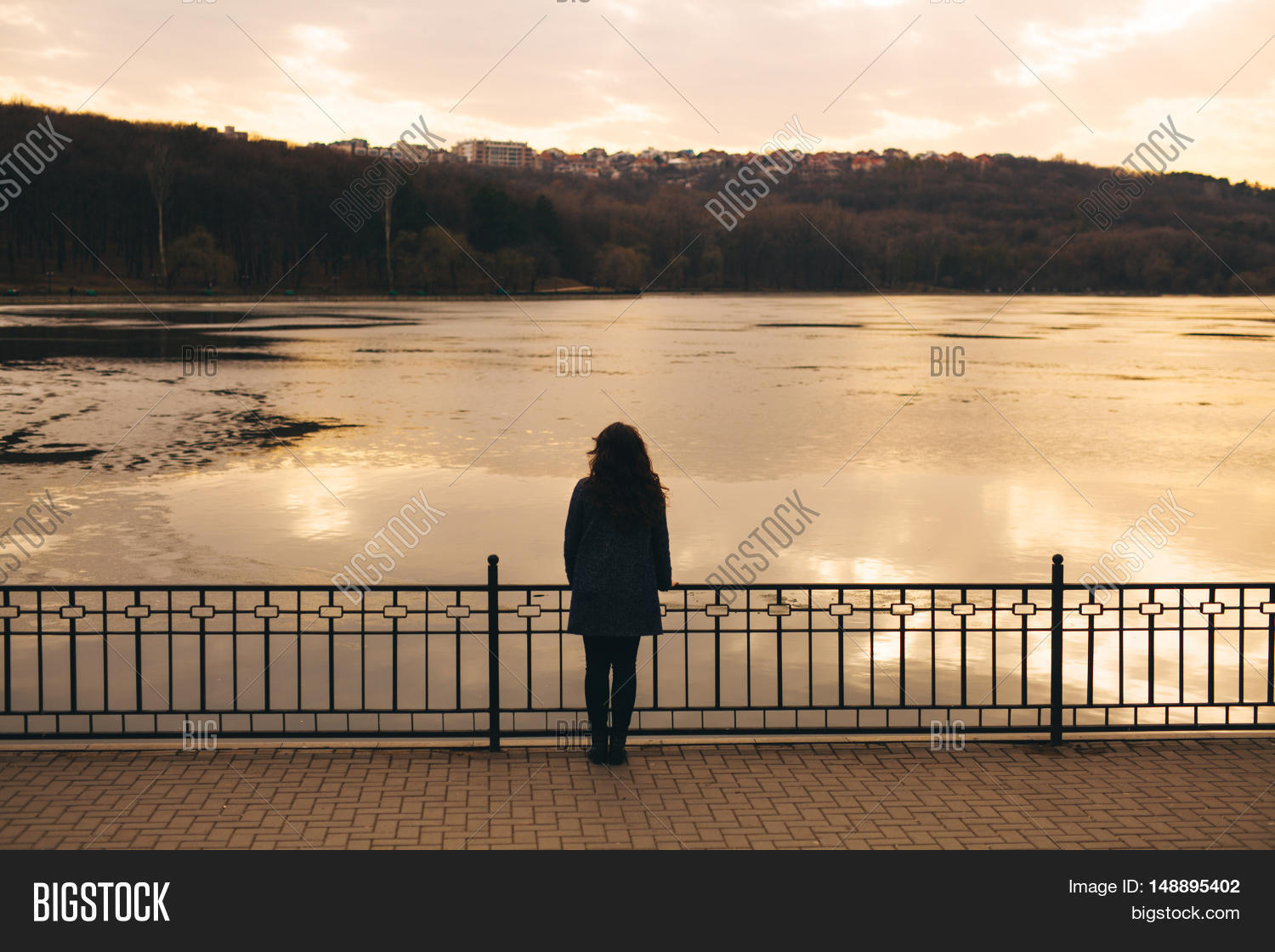 Lonely woman watching sunset alone in winter at sunset sad abstract concept of girl silhouette