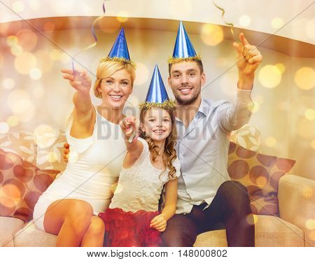 celebration, family, holidays and birthday concept - happy family in blue hats with cake