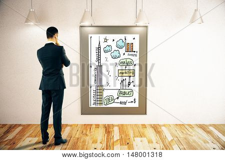 Thoughtful young businessman looking at picture frame with creative business sketch in interior with ceiling lamps concrete wall and wooden floor. Brainstorming concept. 3D Rendering