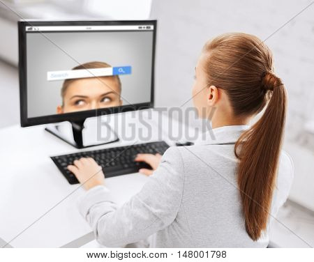 business, people, technology and education concept - businesswoman or student girl with internet browser search bar on computer screen sitting at office table