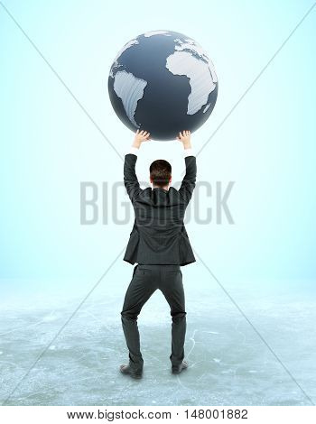 Back view of young businessman holding terrestrial globe on light blue background. 3D Rendering. International business concept