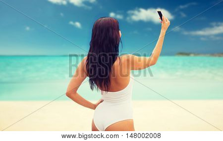 summer, travel, technology and people concept - sexy young woman taking selfie with smartphone over tropical beach background