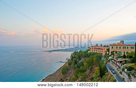 The sunset over Ionian Sea coast from the slopes of Taormina with Giardini Naxos resort on the background Sicily Italy.