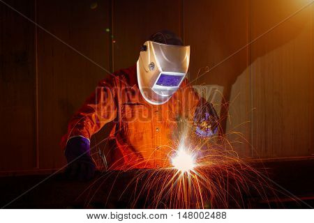 Worker with protective mask welding metal in warehouse industrial.