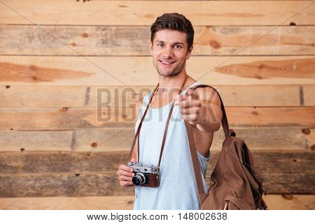 Smiling happy man with backpack and photo camera pointing finger at camera isolated on a wooden background