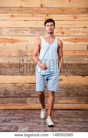 Full length portrait of a handsome fitness man walking and looking at camera isolated on a wooden background