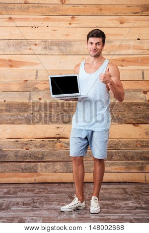 Full length portrait of an attractive smiling casual man holding blank screen laptop and showing thumbs up gesture isolated on a wooden background