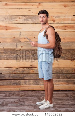 Portrait of cheerful young man with backpack using tablet isolated on a wooden background