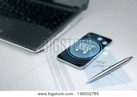 business, technology, sale and commerce concept - close up of smartphone with shopping cart on screen, laptop computer and chart with pen on office table
