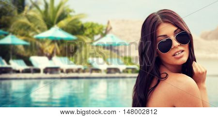 summer vacation, tourism, travel, holidays and people concept -face of young woman with sunglasses over beach and swimming pool background