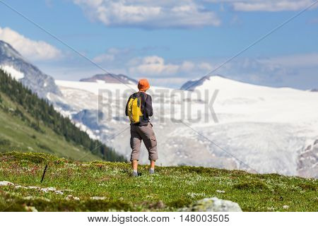 Hiking man traveling in the picturesque mountains on sunny day