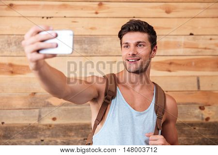 Cheerful attractive young man with backpack taking selfie with smart phone isolated on a wooden background