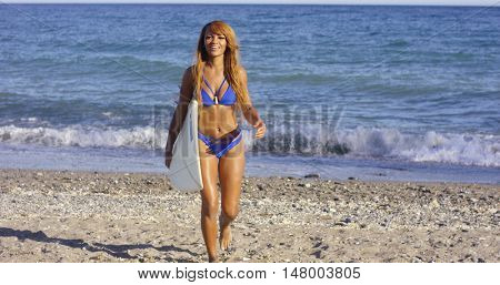 Sexy tanned woman walking with her surfboard