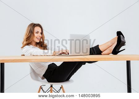 Happy young businesswoman sitting and using laptop with legs on table over white background