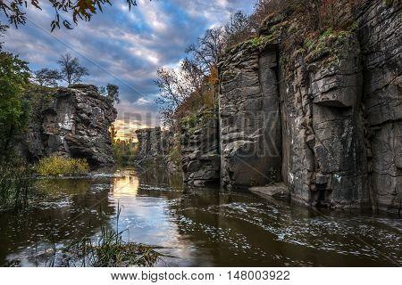 Buky Canyon (River Hirs'kyi Tikych - Ukraine) in autumn season. Beautiful clouds reflect in water.